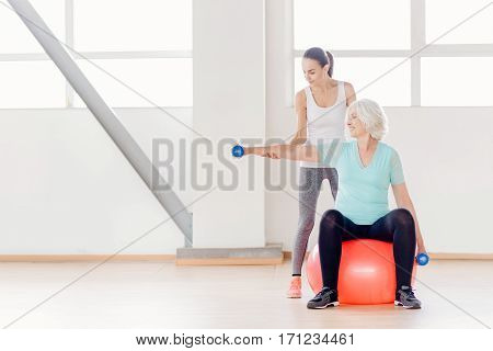 Sports equipment in use. Cheerful pleasant elderly woman sitting on the fitness ball and holding dumbbells while exercising in the gym