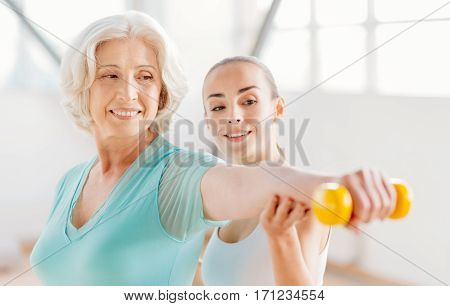 Building up strength. Delighted pleasant elderly woman holding a yellow dumbbell in front of her and looking at it while working out with the fitness coach
