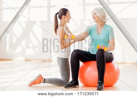 Fitness workout. Positive joyful elderly woman holding dumbbells and exercising with them while sitting on the fitness ball