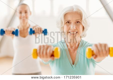 Exercises with dumbbells. Happy delighted aged woman looking at you and exercising with dumbbells while standing in front of her fitness coach
