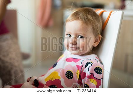 Cute little girl in flower pajamas sitting on chair in the kitchen, smiling