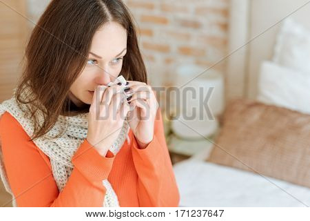 Feeling bad. Ill disappointed young woman sitting on the bed at home and suffering from influenza while holding hanky and touching her nose