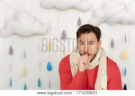 Common winter illness. Sick bearded young man standing isolated in white background at home and suffering from influenza while coughing