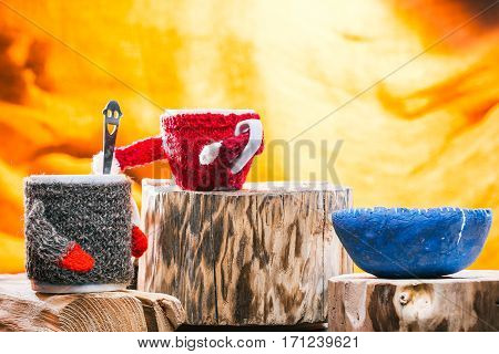 Little tea cup in sweater mixing sugar in big tea mug. Concept of family tea