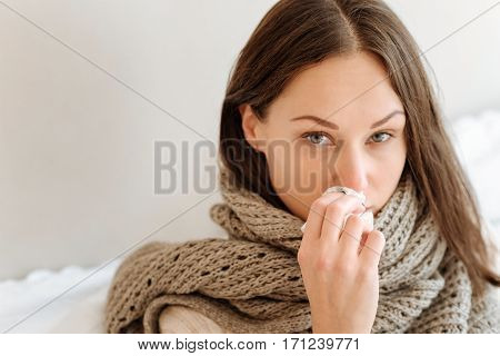 Tired from being ill. Upset powerless young woman standing at home and suffering from influenza while holding handkerchief and touching her nose