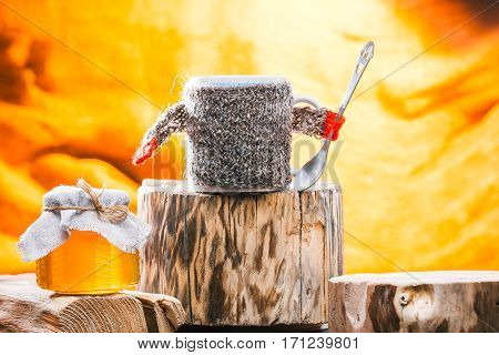 Tea mug wearing sweater and  jar of honey on rustic wood stands on fire background