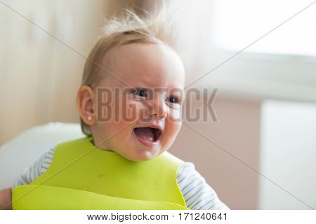 Cute little girl with green bib sitting in high chair laughing