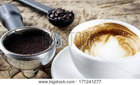 Cappuccino coffee. A cup of latte, cappuccino or espresso coffee with milk put on a wood table with dark roasting coffee beans. Drawing the foam milk on top.
