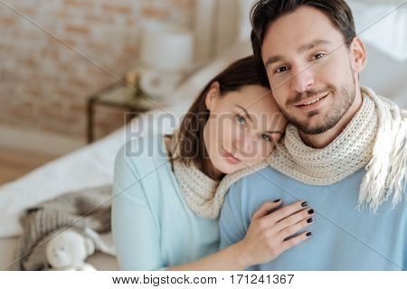 Full of tenderness. Peaceful smiling glad couple sitting on the bed at home and hugging each other while expressing happiness and love