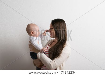 Beautiful young mother in striped red t-shirt holding her baby son in her arms, little boy touching her nose. Studio shot on white background.