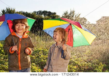 two happy brother with umbrella summer outdoors