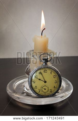Close up view of old fashioned glass candlestick with a burning candle and vintage pocket watch