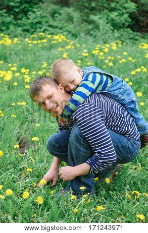 father rode on the back of a young son in a meadow