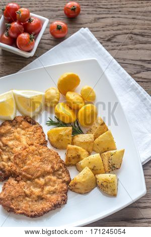 Portion of schnitzel with garnish on the wooden table