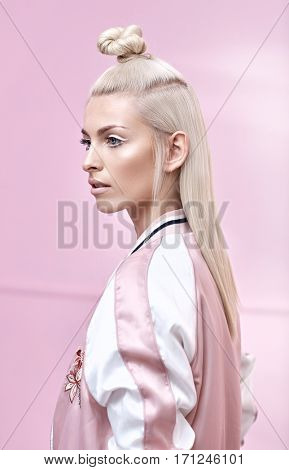 Glamour blond woman posing on pink background