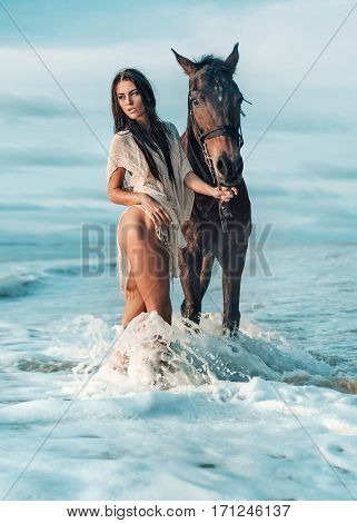 Pretty young woman next to a horse by the sea