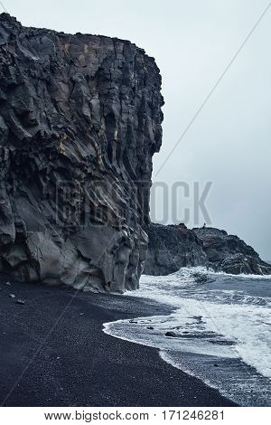 black beach in Iceland. Bank of the Ocean with black sand and cliffs