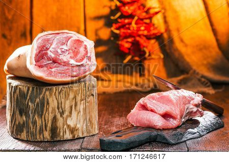 Raw meat pieces on the butcher block and cutting board. Chili pepper string on wooden wall