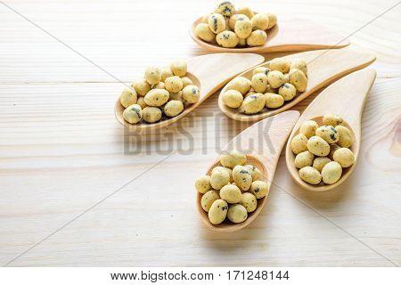 Coated peanuts seaweed flavor in wood spoon on wooden table