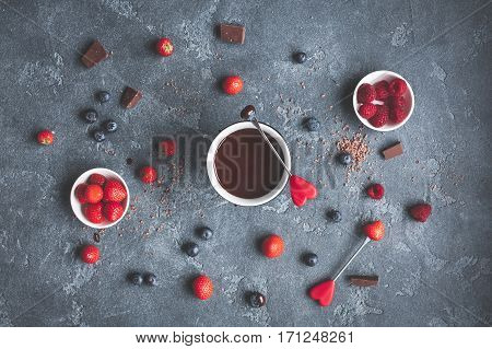 Chocolate fondue with fresh berries on dark background. Valentine's Day. Flat lay top view