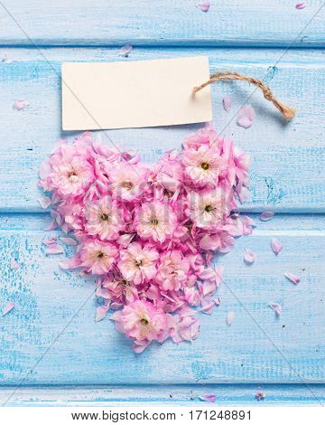 Heart from pink flowers and petals and empty tag on blue wooden planks. Selective focus. Place for text. Toned image.