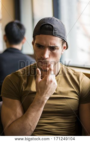 Vertical indoors shot of handsome young pensive man scratching a cheek.