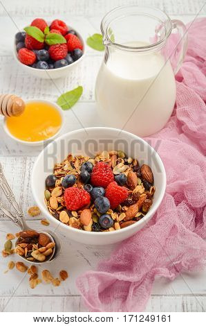 Homemade granola with fresh berries on white wooden background, selective focus