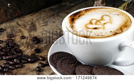In love coffee. Cappuccino coffee. A cup of latte, cappuccino or espresso coffee with milk put on a wood table with dark roasting coffee beans. Drawing the hearts with foam milk on top.