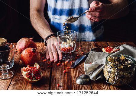 Man Puts Granola into the Glass. Series on Prepare Healthy Dessert with Pomegranate Granola Cream and Jam