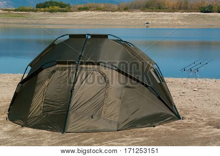 Landscape with fishing rods and hiking tent. Equipment for carp fishing with three fishing rods with reels on a support system - rod pod.