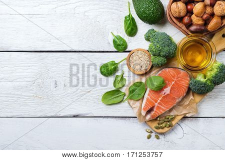 Selection of healthy fat sources food, salmon fish avocado olive oil pumpkin seeds nuts broccoli green spinach on a white rustic wooden table. Copy space background, top view flat lay overhead