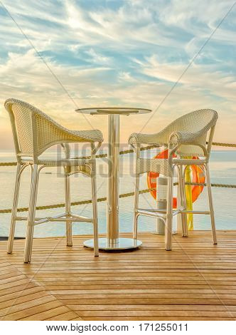 Bar table and two bar stools made of rattan on the wooden deck amid the picturesque sunset