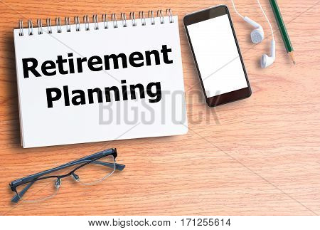 Retirement planning on blank notebook with smart phone and earphone on wooden table top view with copy space. Business concept for any design