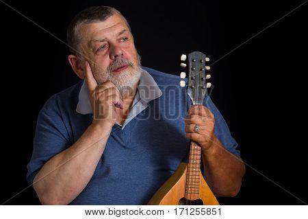 Low key portrait of a bearded senior with mandolin