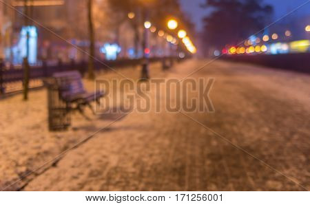 Blurry background - Empty illuminated street at winter night Dnepr city Ukraine