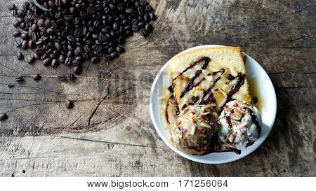 Butter cake with ice cream and the dark roasting coffee beans on wood table.