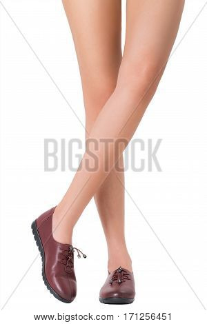 Woman beautiful long legs and healthy skin in crossing legs pose wearing vintage fashion leather shoes Isolated on white background.