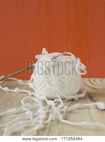 Handmade crocheted white cotton organic lace crochet ball and a hook. Needlework creative craft Tender Mori Girl lace style. Selective soft focus