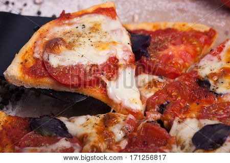 A slice of homemade Italian pizza with mozzarella, Basil and tomatoes. Vegetarian food.