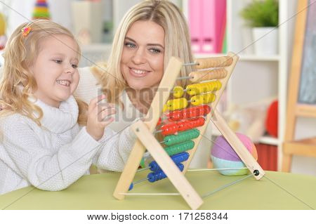 mother with little daughter counting on counter