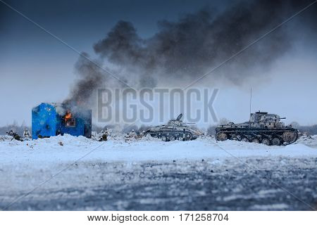 Winter view of the german tanks (panzers) in the attack with burning house. Reconstruction of the winter defensive battles of the Red Army in WWII (1944 year).
