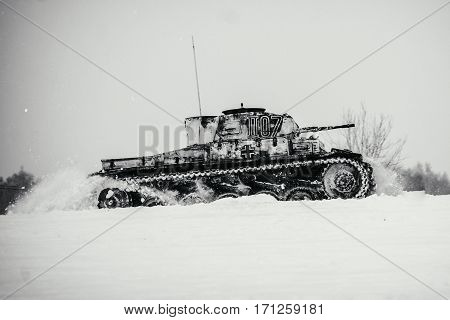 Winter view of the german WWII tank (panzer) Pz. II in attack. Reconstruction of the winter defensive battles of the Red Army in WWII (1944 year). Black and white photo.