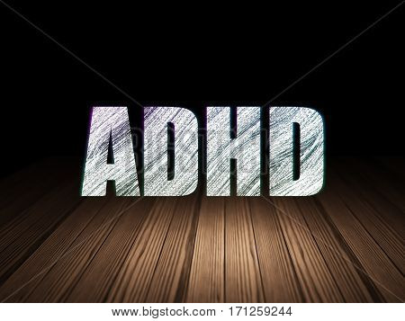 Medicine concept: Glowing text ADHD in grunge dark room with Wooden Floor, black background