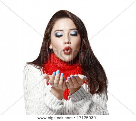 portrait of beautiful young woman in sweater and red scarf blowing in her hands isolated on white in photostudio