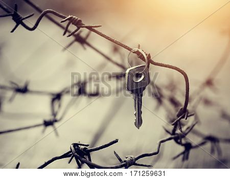 The key hangs on a rusty barbed wire.