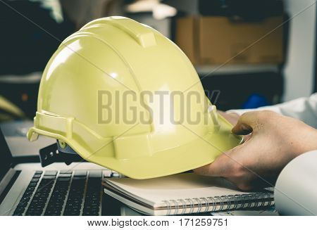 Construction office worker holding Yellow Construction Helmet