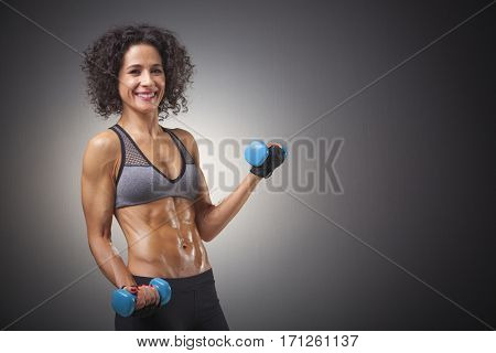 Smiling fitness woman lifing weights on grey background