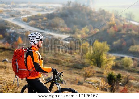 Young bicyclist standing and looking to mountains. Extreme travel in the countryside. Cyclist in the helmet and glasses with red backpack. Beautiful landscape with road and hill. Spring season.