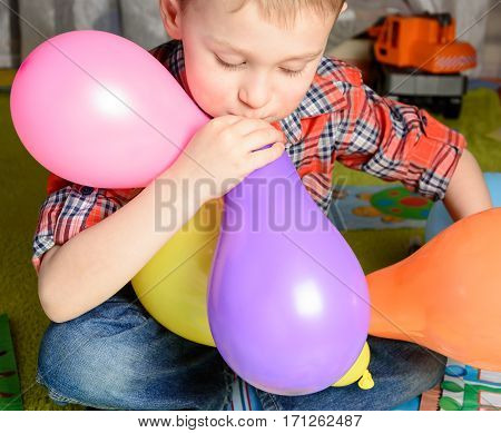 little boy inflates colored balloons sitting on the floor