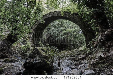 Stone ruins of the Byzantine bridge in a dense forest in Greece